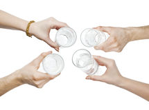 Hands holding water glasses cheering Stock Photo