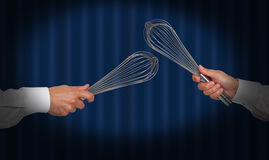 Hands holding whisks Stock Image