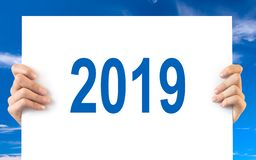 Hands holding a white board with 2019, blue sky. Background royalty free stock photography