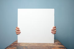 Hands holding white board at desk Royalty Free Stock Photography