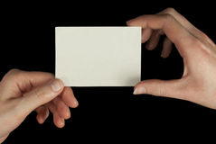 Hands holding a white card. Isolated on black background Royalty Free Stock Image