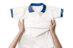 Hands holding a white clean shirt. Hands holding a white clean polo shirt royalty free stock photography