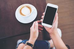 Hands holding white mobile phone with blank black screen with coffee cup on wooden table and floor background. Mockup image of hands holding white mobile phone Royalty Free Stock Photo