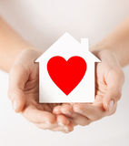Hands holding white paper house Stock Photo