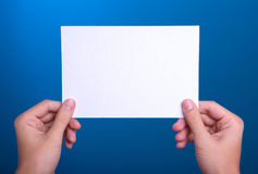 Hands holding white sheet paper card on blue. Close-up hands holding white sheet paper card on blue Stock Photo