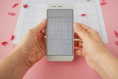 Hands holding white smartphone on paper calendar background. Bright pink clips and pins are scattered around. stock photography