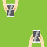 Hands holding white smartphones on a green background. Vector illustration in flat design. Royalty Free Stock Photography