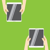 Hands holding white tablet computers on a green background. Vector illustration in flat design. Royalty Free Stock Photo