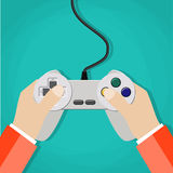 Hands holding wired old school gamepad. Stock Images