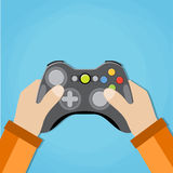 Hands holding wired old school gamepad. Royalty Free Stock Images