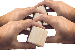 Hands holding wooden blocks. Four hands holding wooden blocks Royalty Free Stock Photography