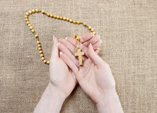 Hands holding wooden brown rosary Royalty Free Stock Images