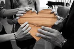 Hands holding wooden heart Stock Images