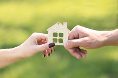 Hands holding a wooden house. Male and female hand holding a wooden house Royalty Free Stock Photography