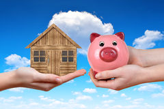 Hands holding wooden house and piggy bank. Stock Photography