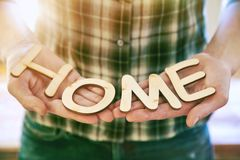 Hands holding wooden letters with word Home Stock Photo