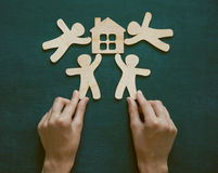 Hands holding wooden men and house Stock Photography