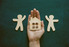 Hands holding wooden men and house stock photo