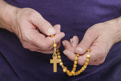 Hands holding wooden rosary Stock Photos
