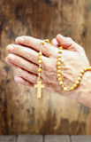 Hands holding wooden rosary Stock Images