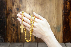 Hands holding wooden rosary Stock Photo