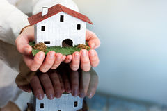 Hands holding wooden toy house. Close up of female hands holding small wooden house Royalty Free Stock Image