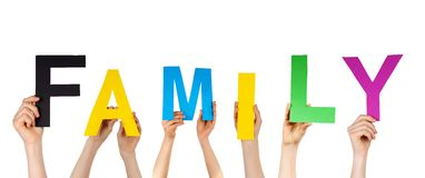 Hands holding the word family. Many hands holding letters building the word family, isolated stock image