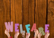 Hands holding word Welfare against wooden background. Composite image of hands holding word Welfare against wooden background royalty free stock photography