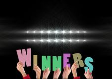 Hands holding word Winners against spot light background. Digitally composite image of hands holding word Winners against spot light background stock image