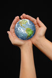 Hands holding the world. On a black background Stock Photography