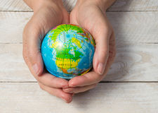 Hands holding world globe on wood. Female hands holding small globe showing top of world, united states and canada on wooden background Royalty Free Stock Image