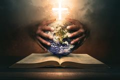 Hands holding the world on a Holy Bible