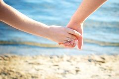 Hands holding of young couple in love while they are enjoying royalty free stock image