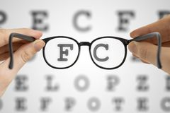 Hands holds black glasses in front of vision testing chart. Eye sight testing concept Stock Photo