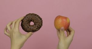 Hands holds donut and apple. Choice donut against apple. Healthy or junk food stock image