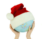 Hands holds globe with Santa's hat Stock Images