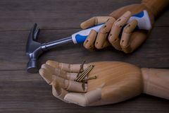 Hands holds a hammer and nails. Hands holds a hammer  and nails on a wooden background Stock Photography