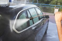 Hands with hose washing car. Cleaning cars stock photos