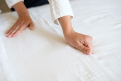Hands of hotel maid making  bed. Hands of hotel maid making a room bed Royalty Free Stock Images