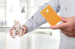 Hands with house and credit card, buy house. Concept royalty free stock image