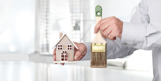 Hands with house and paint brush, home services concept Royalty Free Stock Photo