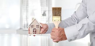 Hands with house and paint brush, home services concept Royalty Free Stock Photography