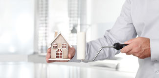 Hands with house and paint roller, home services concept. Hands with house and paint roller, home services painter concept Stock Photo