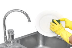 Hands in household gloves. Washing plate Stock Photos