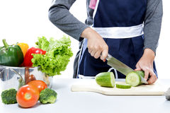 Hands of housewife cutting cucumber Royalty Free Stock Photography