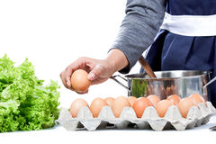 Hands of housewife pick up an egg preparing for making meal Stock Photos