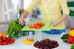 The hands of Housewives during cooking salad. The hands of a young slim woman dressed in a yellow blouse and blue jeans,working on a large bright kitchen cutting Stock Image