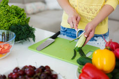 The hands of Housewives during cooking salad. Hands of a young slim woman wearing a yellow shirt and blue jeans,dealing with a large bright kitchen cutting fresh Royalty Free Stock Photo
