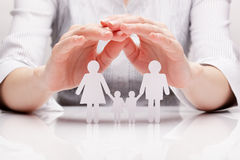 Hands hug the family (concept). Girl protects the family made of paper in his hands stock photo