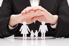 Hands hug the family (concept). The guy in the suit protects the family is made of paper stock photo